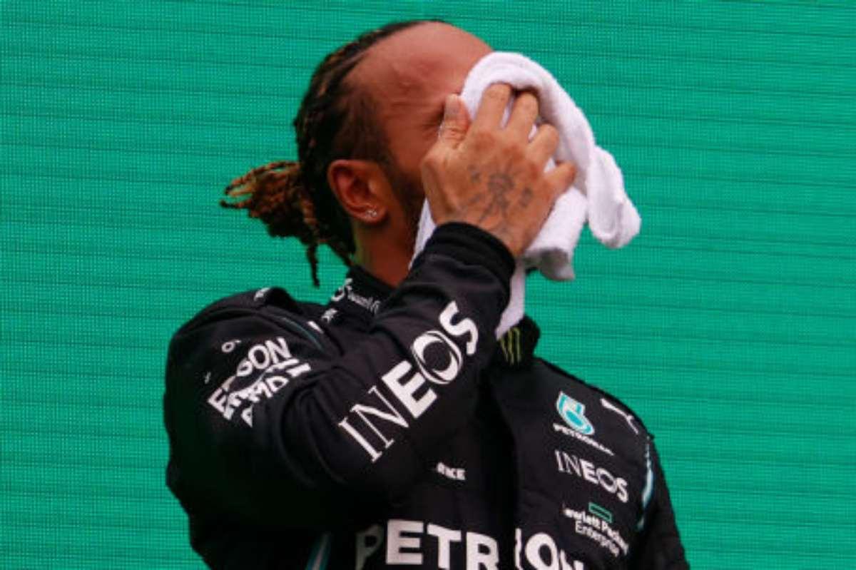 Lewis Hamilton si deterge il sudore sul podio del Gran Premio d'Ungheria di F1 2021 a Budapest
